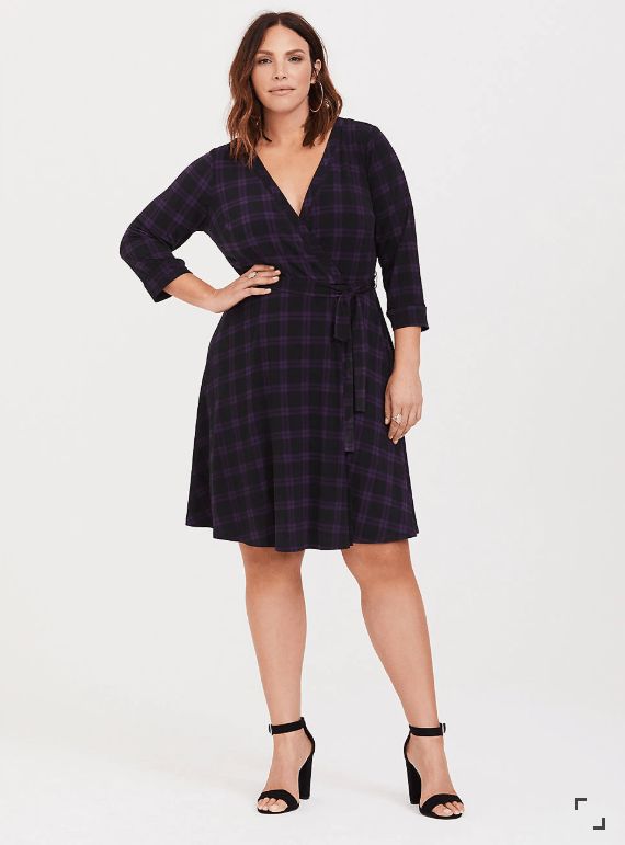 Woman wearing purple and black plaid wrap dress